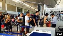 Du khách xếp hàng lên máy bay tại phi trường Tân Sơn Nhất (VOA/Reasey Poch).