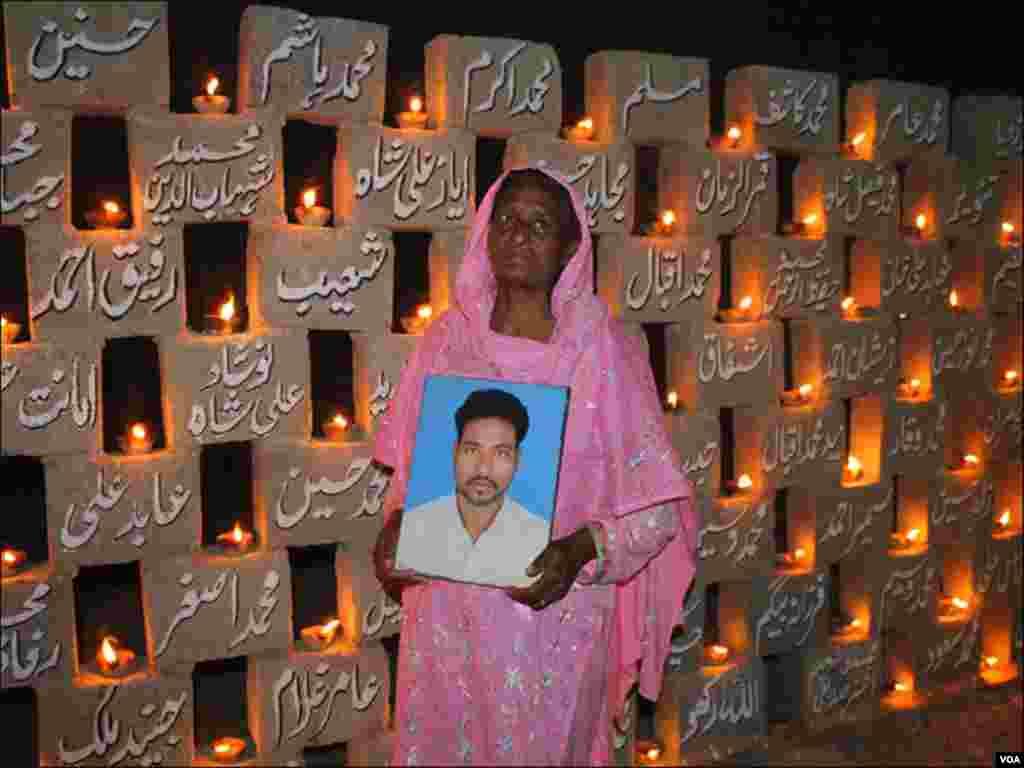 ایک خاتون فیکٹری سانحے میں جان سے گزرنے والے اپنے بیٹے کی تصویر اٹھائے ہوئے ہیں