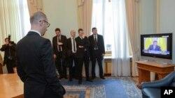 PM Ukraina Arseniy Yatsenyuk (depan kiri) menyaksikan pidato presiden terguling Ukraina Viktor Yanukovych dari Rostov-on-Don, sebuah kota di Rusia, yang ditayangkan dalam acara berita di televisi di Kyiv, Ukraina (28/2).
