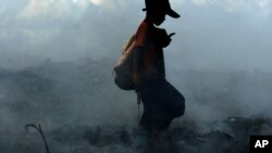 Smoke from burning trash fires swirls around a Cambodian boy as he scavenges a dump on the outskirts of Phnom Penh, file photo.