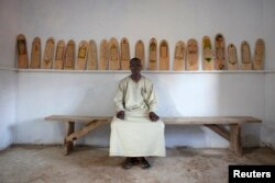 FILE - Aboubakar Yaro, head of conservation at the Djenne Library of Manuscipts, sits next to Koranic scripts written on pieces of wood in Djenne, Mali, Sept. 1, 2012.