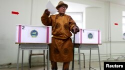 A man wearing traditional Mongolian clothes casts his vote at a polling station during Mongolia's presidential elections in Ulan Bator June 26, 2013. REUTERS/Mareike Guensche (MONGOLIA - Tags: POLITICS) - RTX1111K