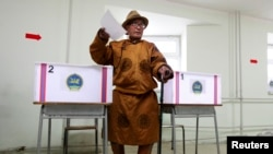 FILE - A man wearing traditional Mongolian clothes casts his vote at a polling station during Mongolia's presidential elections in Ulan Bator June 26, 2013. REUTERS/Mareike Guensche (MONGOLIA - Tags: POLITICS) - RTX1111K