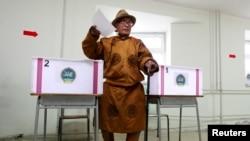 一名身穿传统服装的男子参加蒙古国总统选举,在乌拉巴托的一处投票站投下一票。(2013年6月26日)