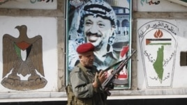 PLO security officer in front of a portrait of the late Palestinian leader at camp Ein el-Hilweh, Sidon, Lebanon, June 19, 2012.