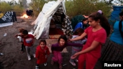 Simona (R), a 11 year-old Roma schoolgirl who has been living in France for 6 years, plays with children near shelters at an illegal camp on the banks of the Var River in Nice, southeastern France, Nov. 6, 2013.