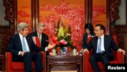 ລັດຖະມົນຕີການຕ່າງປະເທດສະຫະລັດ ທ່ານ John Kerry (ຊ້າຍ) ໂອ້ລົມກັບນາຍົກລັດຖະມົນຕີຈີນ ທ່ານ Li Keqiang ໃນລະຫວ່າງການພົບປະກັນທີ່ກຸງປັກກິ່ງ (13 ເມສາ 2013)