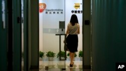 A woman enters an office of GlaxoSimthKline in Beijing, China, July 11, 2013.