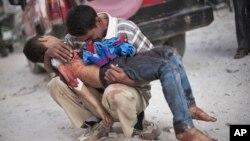 시리아 알레포 시에서 한 남성이 정부군의 폭격으로 사망한 아들의 시신을 안고 통곡하고 있다. (자료사진)