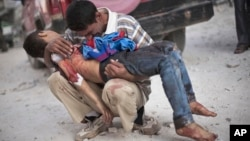 FILE - In this Oct. 3, 2012 file photo, a man cries while holding the body of his son, killed by the Syrian Army, near Dar El Shifa hospital in Aleppo, Syria.