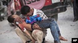 Foto bertanggal 3 Oktober 2012 ini menunjukkan seorang pria menangis sambil menggendong anak laki-lakinya yang tewas di tangan Tentara Suriah dekat rumah sakit Dar El Shifa di Aleppo, Suriah.