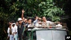 总统大赦释放的服刑人员向他们的家人招手。