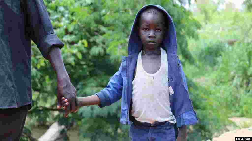 John Wesley, 7 ans, traverse la frontière entre le Soudan du Sud et l'Ouganda avec son père, le 1er avril 2017.