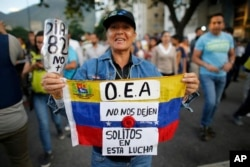 "A demonstrator holds up a Venezuelan national flag with a message that reads in Spanish; ""OAS, don't leave us alone in this fight,"" in Caracas, Venezuela, June 21, 2017."