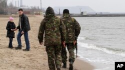 While most of the unrest between Ukrainian forces and pro-Russian separatists are concentrated in the rebel-held areas of Donetsk, local volunteers patrol the city beach in Mariupol, Donetsk region of Ukraine, March 14, 2015.