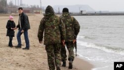 File - Local volunteers patrol the city beach in Mariupol, Donetsk region of Ukraine.