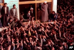 FILE - Ayatollah Ruhollah Khomeini, center, is greeted by supporters in Tehran, Iran, Feb. 2, 1979.