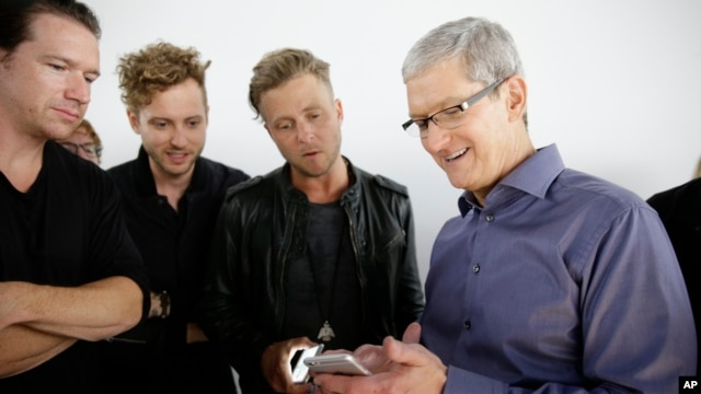Apple CEO Tim Cook, right, looks at the new iPhone 6s with the members of OneRepublic, in the demo room after Apple event at the Bill Graham Civic Auditorium in San Francisco, Sept. 9, 2015.