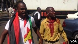 Itai Dzamara with an injured member of Tajamuka-Sesijikile Campaign after they were forced to flee by the police.
