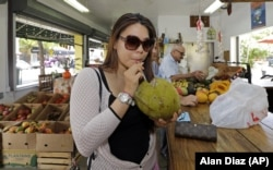 Lillian Nguyen, of New York, drinks coconut water at a fruit store in the Little Havana area of Miami, 2015. (AP Photo/Alan Diaz)