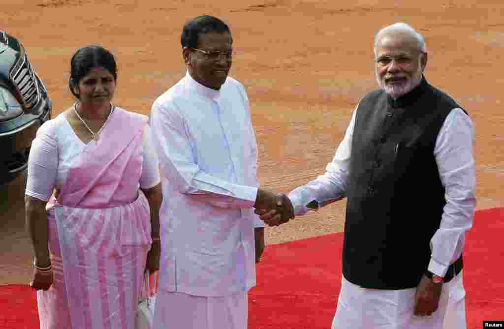Presiden Sri Lanka Mithripala Sirisena (tengah) berjabat tangan dengan Perdana Menteri India Narendra Modi disaksikan istrinya Jayanthi Sirisena dalam upacara penerimaan Sirisena di Istana Presiden Rashtrapati Bhavan di New Delhi (16/2). (Reuters/Adnan Abidi)