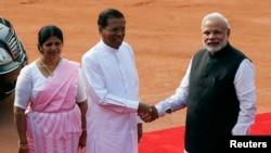 ប្រធានាធិបតីស្រីលង្កា លោក Mithripala Sirisena (កណ្តាល) និងភរិយារបស់លោក គឺលោកស្រី Jayanthi Sirisena ចាប់ដៃជាមួយនាយករដ្ឋមន្រ្តីឥណ្ឌា លោក Narendra Modi (ស្តាំ) នៅឯកិច្ចទទួលស្វាគមន៍មួយនៅវិមានប្រធានាធិបតី Rashtrapati Bhavan ក្នុងទីក្រុងញ៉ូវដេលី កាលពីថ្ងៃទី១៦ ខែកុម្ភៈ ឆ្នាំ២០១៥។