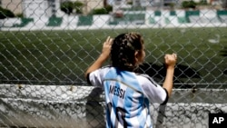 "Twelve-year-old Candelabra Villegas wears a Lionel Messi's national team jersey, in Buenos Aires, Argentina. ""Women are always recognized as less, and we are much more, we are stronger than them and we can achieve much more,"" said Villegas. (AP Photo/Nata"
