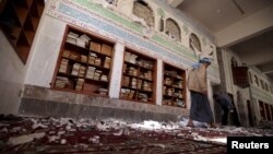 A Houthi militant walks inside the mosque after a suicide bomb attack in Sana'a, Yemen, March 20, 2015.