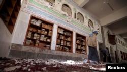 一名也门胡赛武装人员走进首都萨那这座遭自杀炸弹袭击的清真寺内。