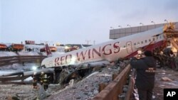 Petugas penyelamat di tempat kecelakaan pesawat di Bandar Udara Vnukovo, Moskow (29/12). (AP/Alexander Usoltsev)