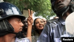 FILE - Lubna Hussein (C), a former journalist and U.N. press officer, gestures outside the court after her trial in Sudan's capital Khartoum, August 4, 2009.