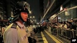 Mong Kok အရပ္မွာ ဆန္႔က်င္ဆႏၵျပသူေတြကို ေစာင့္ၾကည့္ေနတဲ့ အဓိက႐ုဏ္းႏွိမ္နင္းေရး ရဲတပ္ဖဲြ႔ဝင္တစ္ဦး။ (ေအာက္တိုဘာ ၁၉၊ ၂၀၁၄)