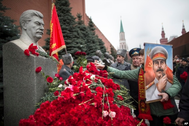 A woman holding a portrait of Josef Stalin places flowers near the monument signifying his grave near the Kremlin wall, marking the anniversary of Stalin's birth, in Moscow's Red Square, Dec. 21, 2017.