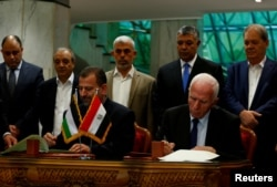 FILE PHOTO - Head of Hamas delegation Saleh Arouri and Fatah leader Azzam Ahmad sign a reconciliation deal in Cairo, Egypt, Oct. 12, 2017.