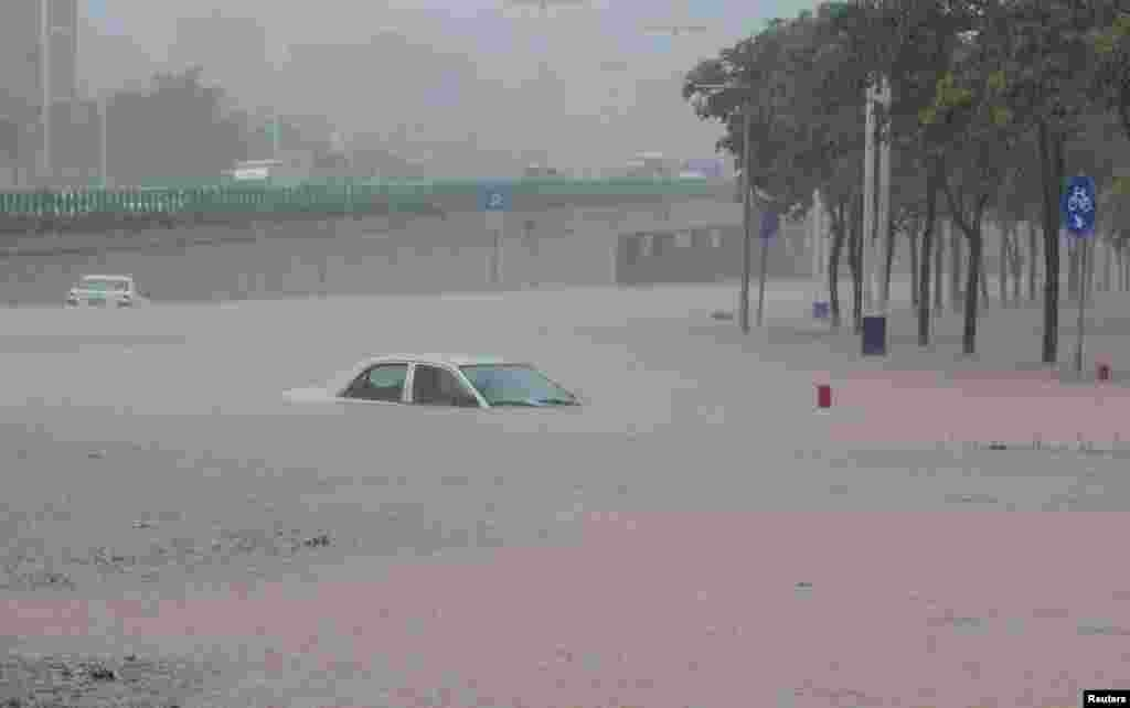 Cars are submerged in a flooded road as heavy rainfall hits Guangzhou, Guangdong province, China.