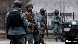 FILE - Afghan policemen stand at the site of a suicide attack in Kabul, February 26, 2015.