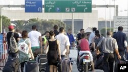 Travelers carry their luggage, as they walk towards the Beirut Rafik Hariri international airport after some of the families of 11 Lebanese pilgrims kidnapped in Syria blocked the highway leading to Beirut airport to protest the Lebanese government's fail