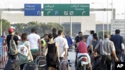 Du khách kéo theo hành lý đi bộ tới phi trường Quốc tế Rafik Hariri sau khi một số thành viên của gia đình 11 người hành hương Li-băng chặn các đường cao tốc dẫn đến sân bay Beirut để phản đối chính phủ Li-băng