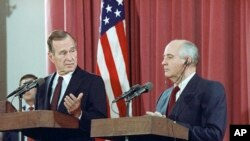 FILE - President George H.W. Bush gestures during a joint news conference with Soviet President Mikhail Gorbachev, at the Soviet Embassy in Madrid, Oct. 29, 1991. Bush died at the age of 94 on Friday, Nov. 30, 2018.