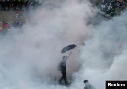 A protester walks in tear gas fired by riot policemen in Hong Kong's financial Central district outside the government headquarters on September 28, 2014.