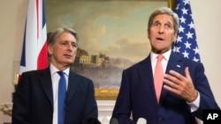 ລັດຖະມົນຕີຕ່າງປະເທດ ສະຫະລັດ ທ່ານ John Kerry, ຂວາ, ຕອບຄຳຖາມກ່ຽວກັບວິກິດການ ໃນຊີເຣຍ ໃນລະຫວ່າງ ກອງປະຊຸມຖະແຫລງຂ່າວ ພ້ອມກັນກັບ ລັດຖະມົນຕີຕ່າງປະເທດ ອັງກິດ ທ່ານ Philip Hammond ຢູ່ໃນນະຄອນຫຼວງລອນດອນ, ວັນທີ 19 ກັນຍາ 2015.