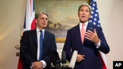 Menteri Luar Negeri AS John Kerry, kanan, menjawab pertanyaan tentang krisis berkepanjangan di Suriah dalam sebuah konferensi pers dengan Menteri Luar Negeri Inggris Philip Hammond, 19 September 2015, di London.