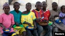 Children displaced as a result of Boko Haram attacks in the northeast region of Nigeria, eat their meal at a camp for internally displaced persons (IDP) in Yola, Adamawa State, Jan. 13, 2015.
