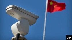 一面中国国旗在监控北京十字路口的海康威视安全摄像头附近飘扬。(2019年10月8日)