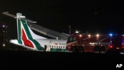 Firefighters are seen next to a an ATR 72 airliner of Romanian carrier Carpatair at Rome's International Leonardo Da Vinci airport, in Fiumicino, outskirts of Rome, Feb. 2, 2013. A 7-year-old Syrian girl suffering from a rare form of cancer arrived in Italy on Thursday.