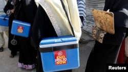 FILE - Polio vaccinators carry boxes of vaccine drops as they head toward sites where they will administer them in Karachi, Pakistan, Oct. 21, 2014.