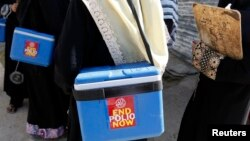FILE - Polio vaccinators carry boxes of polio vaccine drops as they head to the areas they have been appointed to administer the vaccine, in Karachi, Oct. 21, 2014.