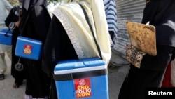 Tim vaksinasi polio membawa kotak-kotak vaksin polio menuju wilayah tempat mereka ditugaskan untuk memberikan vaksin, di Karachi, 21 Oktober 2014. (Foto: dok.)