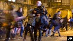 Một người đàn ông ôm hai em bé giữa đám đông hoảng loạn tại vụ tấn công nhà hàng Le Petit Cambodge, Chủ nhật ngày 15 tháng 11 năm 2015.