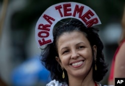 "A reveler wears a crown that reads in Portuguese: ""Out Temer"" during a carnival street party in Rio de Janeiro, Feb. 24, 2017. Merrymakers took to the streets to protest Brazil's President Michel Temer."